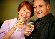 Man and woman smiling and holding up wine glasses, close up