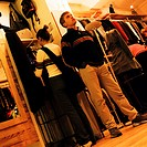 Young woman looking at clothes in clothing store, and young man standing with hands in pockets