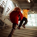 Young people walking up stairs in elevated subway station