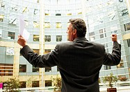 Businessman standing in front of building, arms raised in victorious gesture, rear view