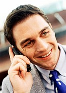 Businessman using cellular phone, close-up, portrait