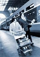 Businessmen walking next to train on platform, b&w