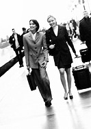 Businesswomen walking together on platform, blurred, b&amp;w