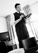 Businessman standing looking at agenda in hotel room, open laptop on bed in foreground, b&w