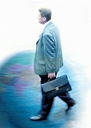 Businessman walking with briefcase on globe, montage