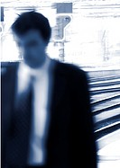 Businessman standing on platform, blurred