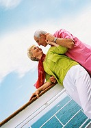 Mature woman looking at senior man, leaning on rail of boat