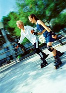 Mature woman and girl in-line skating, blurred
