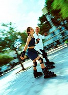 Mature woman and young girl in line skating, blurred