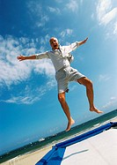 Mature man jumping on trampoline at the beach