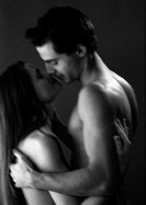 Nude man and woman embracing, blurred black and white