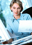 Businesswoman holding documents, looking at computer