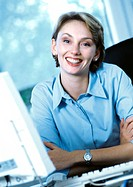 Businesswoman at desk, smiling at camera, portrait