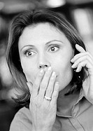 Woman using cell phone, hand over mouth, close-up, B&W