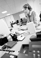 Businesswoman wearing headset in office, side view, B&W