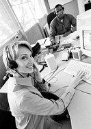 Businesswoman and colleague wearing headsets, B&W