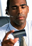 Businessman wearing headset, looking down at credit card in hand, close-up