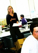 In office, woman standing with document, gesturing, other people working