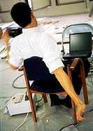 Man sitting in chair stretching arms, in front of laptop computer on chair