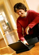Man using laptop computer on floor