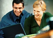 Businessman and woman with laptop computer, smiling