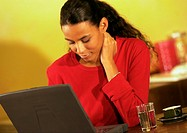 Woman working on laptop with hand on neck