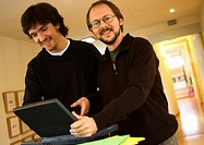 Two men with laptop computer, smiling