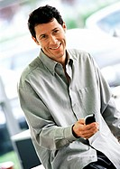 Man holding cell phone in front of him, smiling, waist up