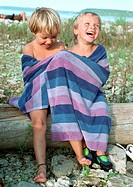 Girl and boy in bath towel sitting on log, smiling