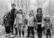 Children side by side in forest, b&w