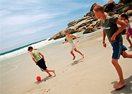 Young people playing soccer at the beach