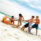 Group of people playing tug of war on the beach
