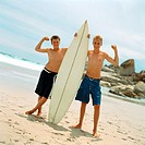 Two boys on beach holding surfboard