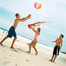 Two boys playing with beach ball, woman holding kite