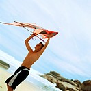 Teenage boy holding kite at the beach