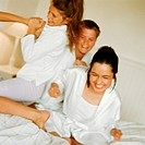Young people playfighting on bed, smiling