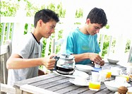 Two teenage boys having breakfast outside