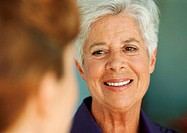 Senior woman looking at younger woman, close-up, blurred foreground
