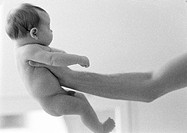 Man's arm holding out naked infant, side view, b&w