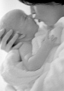 Mother kissing infant, side view, b&w
