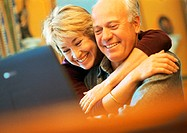 Mature couple smiling, man using laptop, woman with arms around man