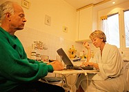 Mature couple in kitchen, woman using laptop, man holding glass