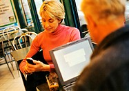Mature couple in restaurant, man using laptop, woman using cell phone