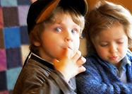 Two children, one looking into camera with finger in mouth, blurred
