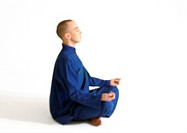 Man sitting in lotus position, meditating, side view