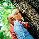 Mature man and woman standing behind tree