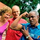 Three people standing outside, man flexing arm muscles