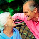 Mature couple face to face, each with one end of piece of candy in mouth between them