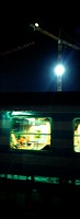 Subway train at night, crane and flood light in background, blurred