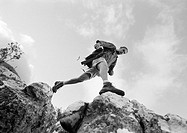 Man stepping across rocks, low angle view, b&w